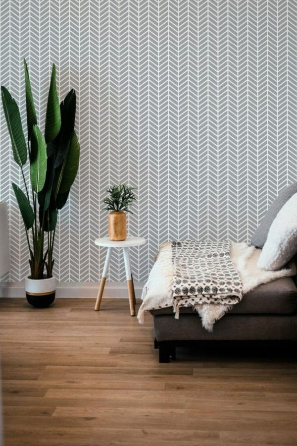 Gray and white herringbone peel and stick wallpaper and sofa in the living room